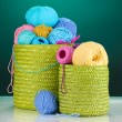 Colorful yarn for knitting in green basket on blue background — Stock Photo #13508650