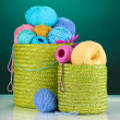 Colorful yarn for knitting in green basket on blue background — Stock Photo