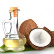 Decanter with coconut oil and coconuts isolated on white — Stock Photo #13508660