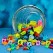 Scattered pieces of paper and colored stones with dreams in glass vase on b - Stock Photo