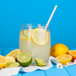 Citrus lemonade in glass bank of citrus around on wooden table on blue back — Stock Photo #13508943
