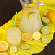 Citrus lemonade in glass and pitcher of citrus around on yellow fabric on w — Stock Photo