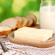 Butter on wooden holder surrounded by bread and milk on natural background — Stock Photo #13508969