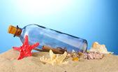 Not etmek içinde kum mavi zemin üzerine cam şişe — Stok fotoğraf