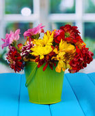 Green pail with flowers on blue wooden table on window background — Stock Photo