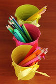 Colorful pencils and felt-tip pens in color pails close-up on wooden table — Stock Photo