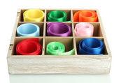 Světlé hedvábné stužky v dřevěné krabici, izolované na bílém — Stock fotografie