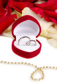 Beautiful box with wedding rings on red, white and pink rose petals backgro — Stok fotoğraf