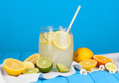 Citrus lemonade in glass bank of citrus around on wooden table on blue back — Stock Photo