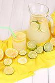 Limonada cítrica en vaso y jarra de cítricos alrededor de tela amarilla en w — Foto de Stock