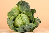 Fresh savoy cabbage on wooden table on beige background — Stock Photo
