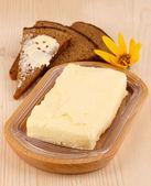 Beurre sur le pain sur close-up de table en bois et support en bois — Photo