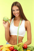 Beautiful young woman with fruits and vegetables, on green background — Stock Photo