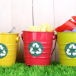 Recycling bins on green grass near wooden fence — Stock Photo #13536775