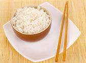 Bowl of rice and chopsticks on plate on bamboo mat — Stock Photo