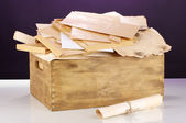 Wooden crate with papers and letters on purple background — Stock Photo