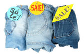Three fashion blue jeans on sale close-up isolated on white — Stock Photo