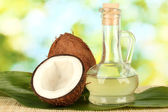 Decanter with coconut oil and coconuts on green background — Zdjęcie stockowe