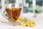 A cup of tea with immortelle on wooden table on window background — Stock Photo