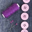 Stock Photo: Colorful sewing buttons with thread on jeans closeup