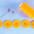 Stock Photo: Colorful sewing buttons with thread on blue fabric