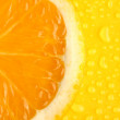 Slice of orange with drop on yellow background — Stock Photo