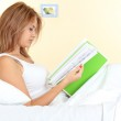 Young beautiful woman in bed reading the magazine — Stock Photo
