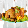 Stock Photo: Chef holding a plate of baked chicken with fruit and spices close-up