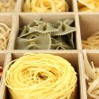 Nine types of pasta in wooden box sections close-up - Stock Photo