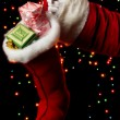 Santa Claus hand holding gifts on bright background — Stock Photo #13542669