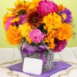 Beautiful bouquet of bright flowers with paper note on wooden table on gree - Foto de Stock