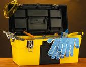 Gele gereedschapskist openen met tools op bruine achtergrond close-up — Stockfoto