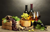 Fat, flaskor och glas vin och mogna druvor på träbord på grå — Stockfoto