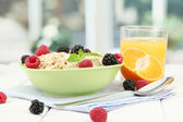 Tasty oatmeal with berries and glass of juice on table, on window backgroun — Stock Photo
