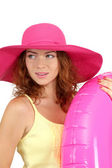 Smiling beautiful girl with beach hat and rubber ring isolated on white — Stock Photo