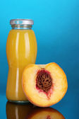 Delicious peach juice in bottle and peach next to it on colorful background — Stock Photo