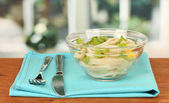 Salad of squid rings, lemon and lettuce in a glass bowl on wooden table clo — Stock Photo