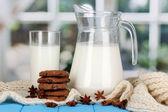 Brocca e il bicchiere di latte con biscotti su colli maglieria su legno tabl — Foto Stock