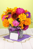 Beautiful bouquet of bright flowers with paper note on wooden table on gree — Stock Photo