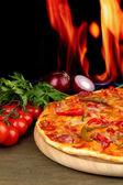 Pizza pepperoni savoureux avec des légumes sur une planche en bois sur fond de flamme — Photo