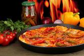 Pizza pepperoni savoureux dans la poêle avec les légumes sur le fond de la flamme — Photo
