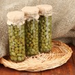 Stock Photo: Glass jars with tinned capers on sack background close-up