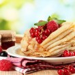 Pancakes with berries, jam and honey on wooden table on green background — Stock Photo #13575003