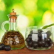 Постер, плакат: Olive oil small decanter on green background close up