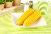 вареная кукуруза и цветы на белом фоне — Стоковое фото