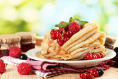 Pancakes with berries, jam and honey on wooden table on green background — Stock Photo