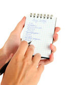 Woman's hand holding a notebook with a shopping list close-up — Stok fotoğraf