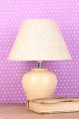 Tischleuchte und buch auf lila polka-dot-hintergrund — Stockfoto