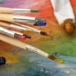 Acrylic paint, paint tubes and brushes on wooden palette — Stock Photo #13580109