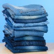 Stock Photo: Many jeans stacked in pile on blue background